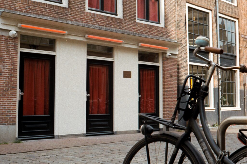 black bicycle parked beside red concrete building