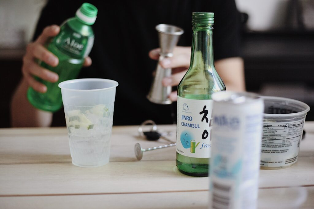 person holding bottle beside table with cup, bottle, and can
