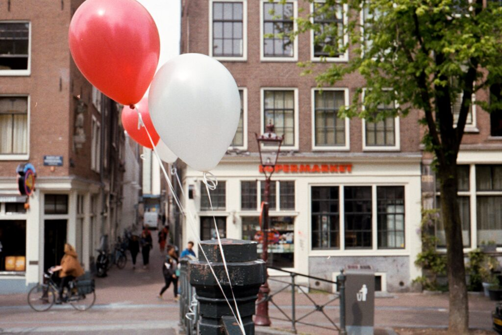 people walking on sidewalk with balloons on the street during daytime
