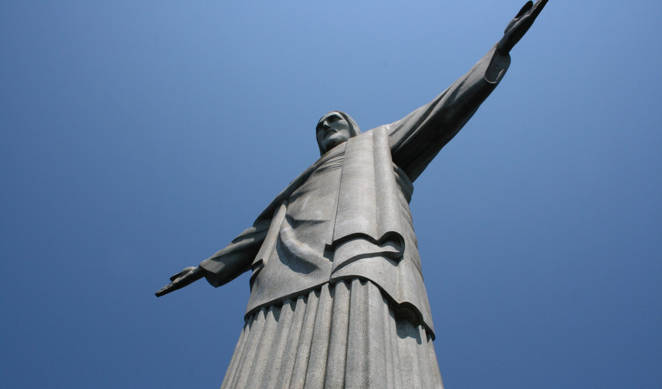 low angle photography of angel statue under blue sky during daytime